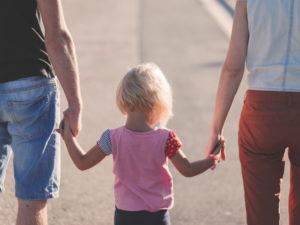 Una bambina passeggia con il papà e la mamma.